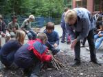 Fleißige und geschickte Hände bauen ein tolles Lagerfeuer aus dem gemeinsam im Wald gesammelten Brennholz.